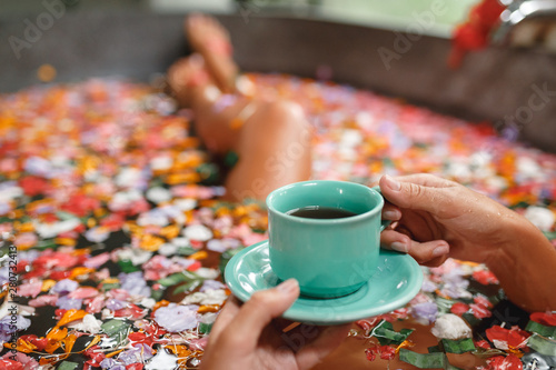 Foto Woman in bath with petals with cup of herbal tea