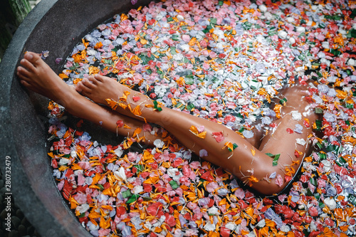 Female legs in bathtub with flower petals and beauty products on wooden tray Tapéta, Fotótapéta