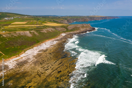 Fototapeta Aerial view of cliffs and waves on the Worm's Head area of the Gower peninsula