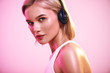Leinwandbild Motiv Music in my soul. Close up of cute blonde woman in headphones listening music and looking at camera while standing against pink background