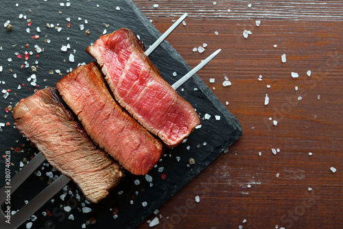 Three pieces of meat on a fork for meat. three types of meat roasting, rare, medium,well done. - 280740628