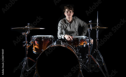 Photo Professional drummer playing on drum set on stage on the black background