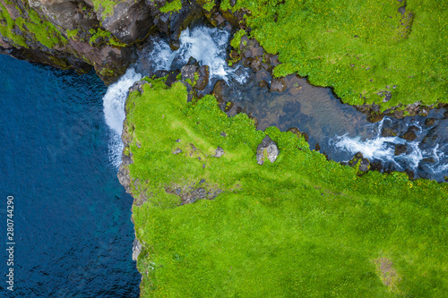 Foto auf Leinwand Blaue Nacht Aerial view of Mulafossur waterfall in Gasadalur village in Faroe Islands, North Atlantic Ocean. Photo made by drone from above. Nordic Natural Landscape.