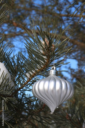 An Evergreen Christmas.White Christmas Tree Ornament On An Evergreen Tree Outside
