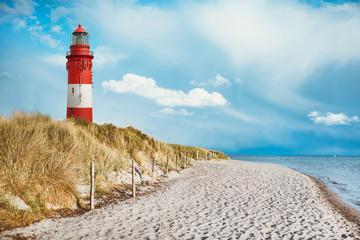 Leuchtturm am Strand einer Insel, an der Küste hinter und auf Düne mit Strandsand und Wasser am Meer. blauer Himmel mit weißen Wolken mit Platz für Text