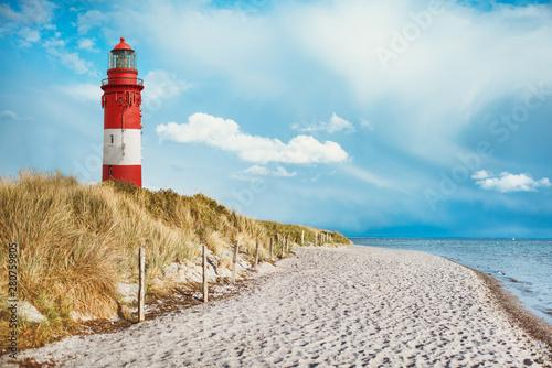 Leuchtturm am Strand einer Insel, an der Küste hinter und auf Düne mit Strandsand und Wasser am Meer Fototapeta