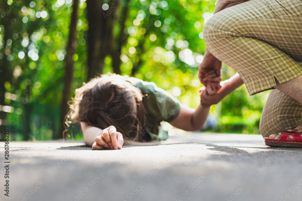 Fototapety, obrazy: Fainted girl helped by an old woman – Teenager lying on the ground while receiving support from an elder