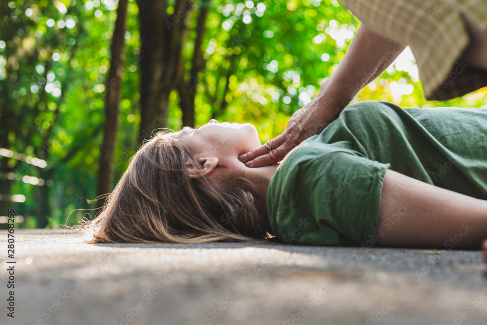 Fototapety, obrazy: Unconscious fainted girl having pulse checked by an old woman – Teenager lying on the ground while her pulse is verified by an elder citizen on teen's carotid artery