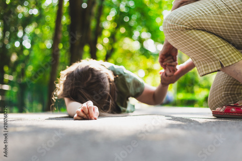 Obraz Fainted girl helped by an old woman – Teenager lying on the ground while receiving support from an elder - fototapety do salonu