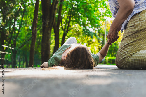 Fainted girl checked by an old woman – Teenager lying on the ground while pulse Wallpaper Mural