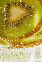 Close Up Of Water With Kiwi Slices And Bubbles