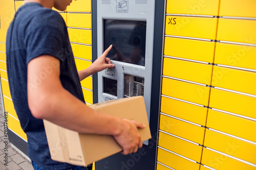 Fototapeta Client using automated self service post terminal machine or locker to deposit a