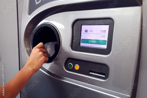 Fotografía  Man returns bottles and cans of reusable packagings in reverse vending machine