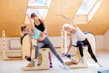 Different Generation Females Is Concentrated On Stretching Exerciseon On Pilates Chair Equipment With Woman Instructor At Studio. Sports Equipment. Active And Healthy Lifestyle Rehabilitation Concept.