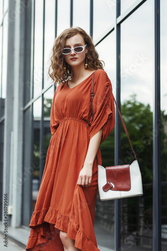 Fotomural Outdoor fashion portrait of young elegant woman wearing orange midi dress, white