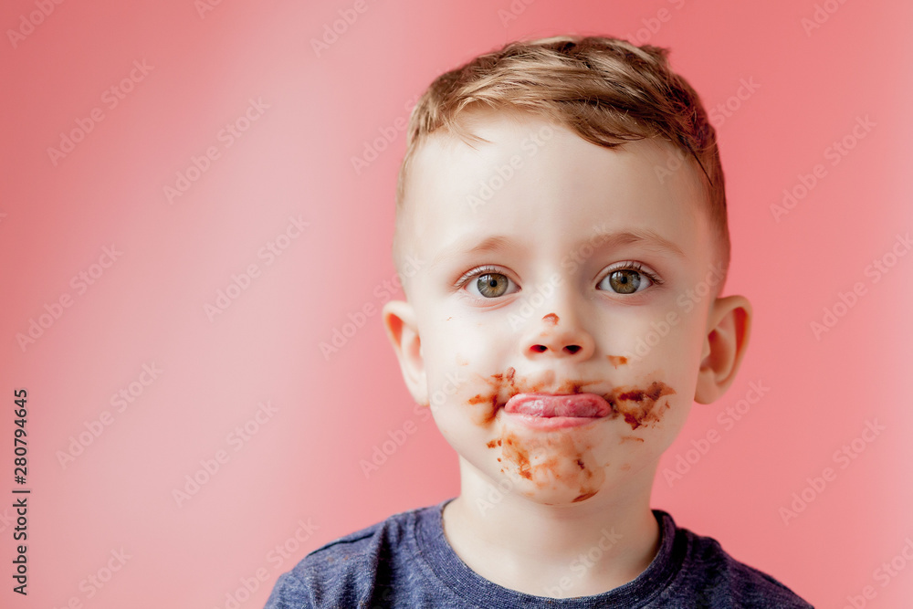 Obraz Little boy eating chocolate. Cute happy boy smeared with chocolate around his mouth. Child concept. fototapeta, plakat