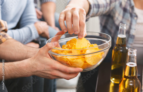 Fotografía  Man holding bowl with chips sharing with friends at party