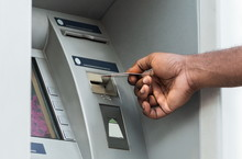 Unrecognizable African Man Putting Credit Card Into ATM