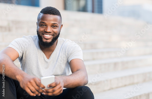 Fototapeta Portrait of casual african guy sitting on stairs and smiling obraz