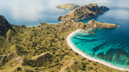 Aerial panoramic view of Padar island in Komodo National Park, Indonesia. Drone shot, top view. Green hills and amazing beautiful coastline. Tropical background.