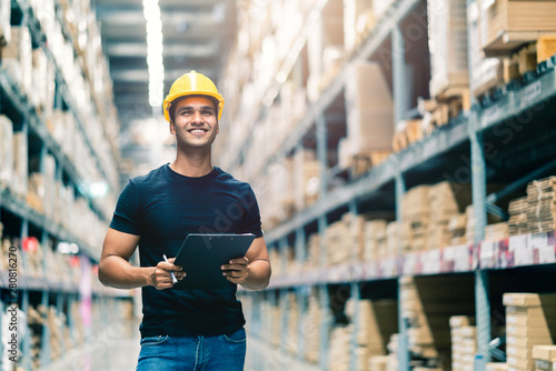 Obraz Smart Indian engineer man wearing safety helmet doing stock tick check and cardboard stock product management in factory warehouse background - fototapety do salonu