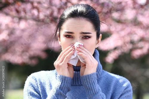 Fotografia, Obraz  Young woman with nose wiper near blooming tree