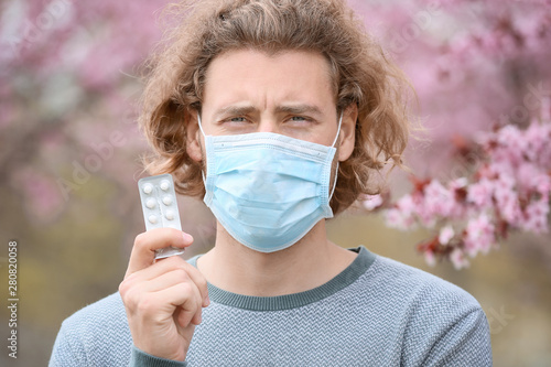 Young man in protective mask and with pills near blooming tree Canvas Print