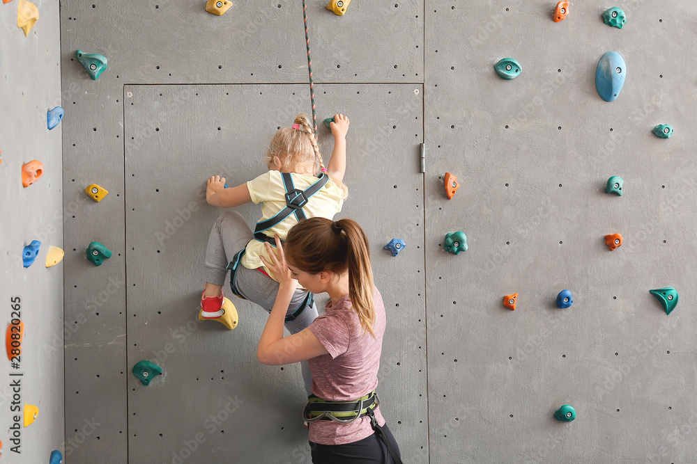 Fototapety, obrazy: Instructor helping little girl to climb wall in gym