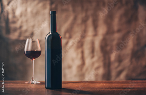 Canvas Prints Alcohol Bottle of wine with a full glass on the sun lighted background. Horizontal shot. Provence.