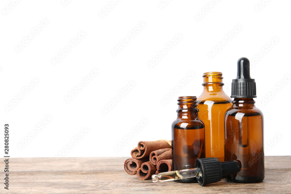 Fototapety, obrazy: Bottles of essential oils and cinnamon sticks on wooden table against white background. Space for text