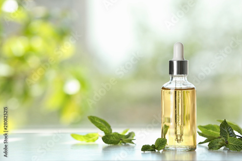 Fototapeta Bottle of mint essential oil on white wooden table against blurred background. Space for text obraz