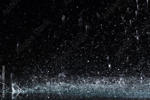 Fotografia, Obraz Heavy rain falling down on ground against dark background