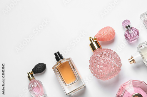 Obraz Different luxury perfume bottles on white background, top view - fototapety do salonu