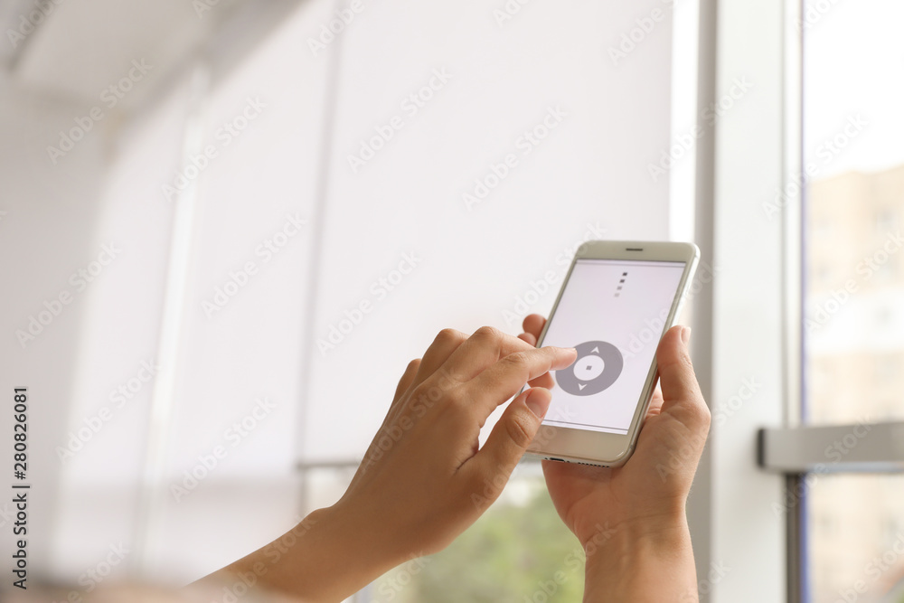 Fototapeta Woman using smart home application on phone to control window blinds indoors, closeup. Space for text