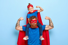 Strong Powerful Dad And Little Female Child On His Shoulders Show Muscles, Ready To Defend You And Struggle, Dressed In Superman Clothes, Isolated On Blue Background, Prentend Having Superhuman Power