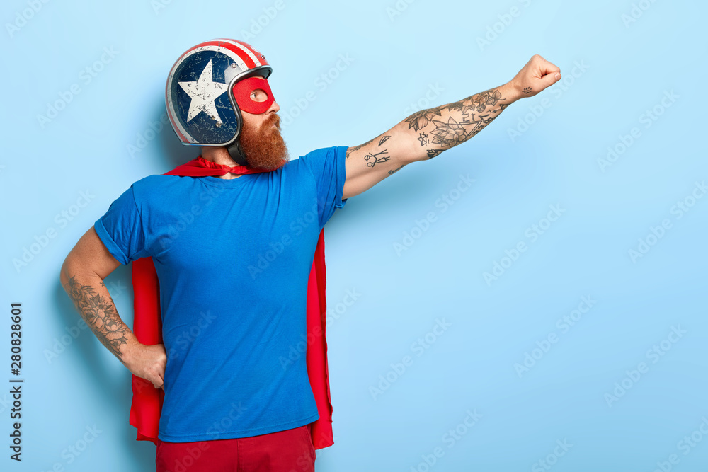 Fototapeta Profile shot of serious bearded man makes flying gesture, looks into distance, wears protective helmet and red cape, poses against blue background with empty space for your promotional content