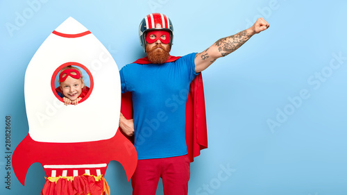 Obraz Serious bearded father raises arm, pretends being superhero, wears helmet, mask, cape and blue t shirt, plays with little daughter who looks through hole of paper rocket. My dad is superman! - fototapety do salonu