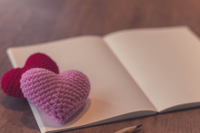 Red And Pink Hearts With Plain Notebook On Wooden Table With Blurred Background