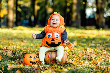 Cheerful Little Baby Boy In Halloween Costume Sitting On Pumpkin, Celebration