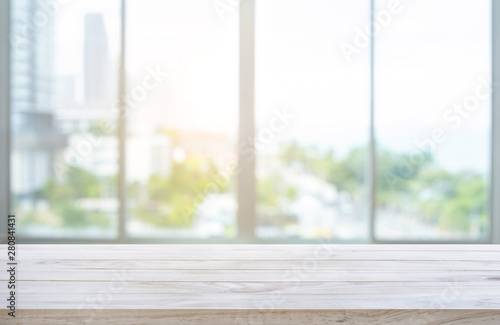 Foto  Wood table top on blur window glass,wall background with city view