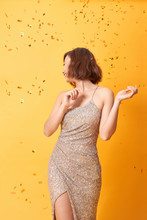 Beautiful Sexy Woman In Evening Dress Celebrating, Golden Confetti, Party, Smiling, Inviting, Happy