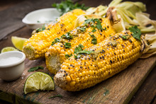 Grilled COrn On Cob With HErbs And Salt. Wooden Rustic Background