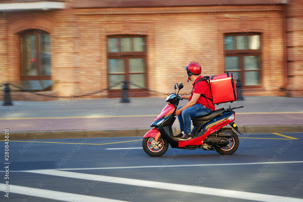 Fototapety, obrazy: Delivery boy of takeaway on scooter with isothermal food case box driving fast. Express food delivery service from cafes and restaurants. Courier on the moto scooter delivering food.