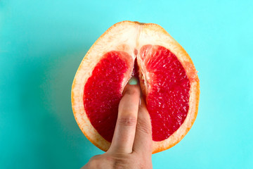 two fingers in a grapefruit isolated on a blue background top view sex concept