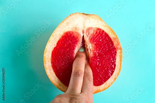 two fingers in a grapefruit isolated on a blue background top view sex concept - 280846297