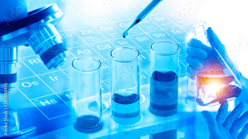 Double Exposure, hand holding flask , scientist dropping blue liquid into test tubes, microscope, periodic table background in laboratory. Science or chemical research and development concept.