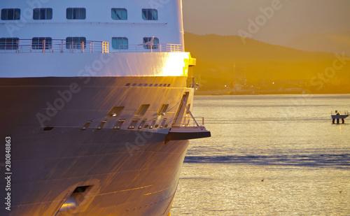 Photo  Offene Ladetür an Bug von Kreuzfahrtschiff mit Hafenanlagen im Hintergrund bei