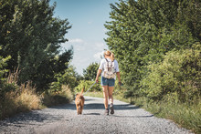 Woman And Dog Walking On Road. Tourist With Backpack Enjoying Walk With Her Animal Best Friend