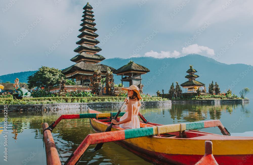 Fototapeta Beautiful girl kayaking on the catamaran at the ulun datu pura bratan temple, in Bali