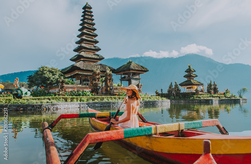 Beautiful girl kayaking on the catamaran at the ulun datu pura bratan temple, in Bali